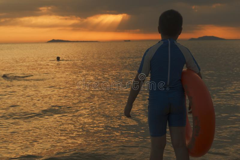 Chinese kid with Swimming ring on beach sunset time royalty free stock images