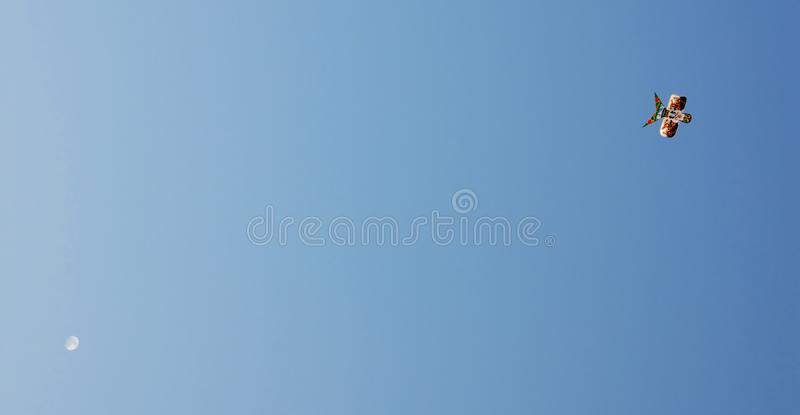 A Chinese kite flying against a blue sky with the moon. Great background for a Chines theme. stock photos