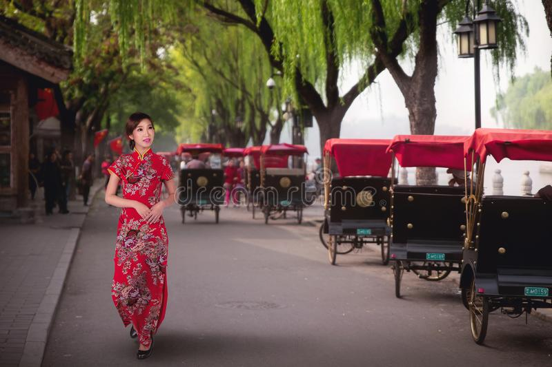 Chinese lady in red cheongsam dress walking near a Tourists riding Beijing traditional rickshaw. In old China Hutongs in Beijing, China royalty free stock image