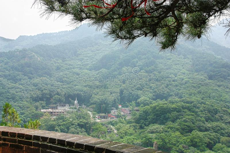Small old monastery among mountains in China, view via fence. Chinese landscape with fogged mountains covered with green forest, branch of pine and small old stock photos