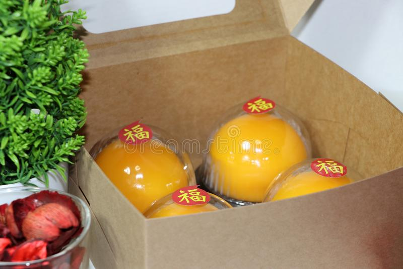 Chinese language : bliss, stick on four orange cakes in the box and out focus green leaf with on white floor. Chinese New Year concept stock images