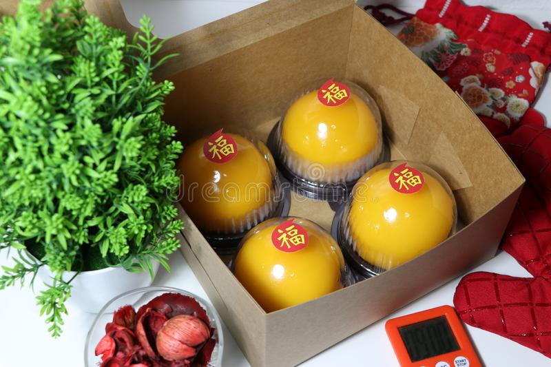 Chinese language : bliss, stick on four orange cakes in the box with red kitchen glove and red fabric bag and green leaf and. Stopwatch with dried flower in the stock images