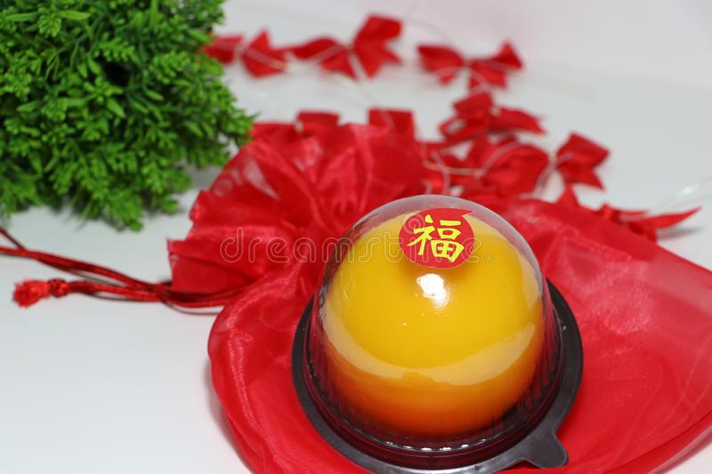 Chinese language : bliss, stick on the orange cake on the red fabric bag and out focus red ribbon and green leaf on white floor. Chinese New Year concept stock photo