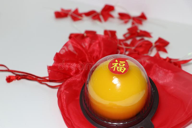 Chinese language : bliss, stick on the orange cake on the red fabric bag and out focus red ribbon on white floor. Chinese New Year concept stock image