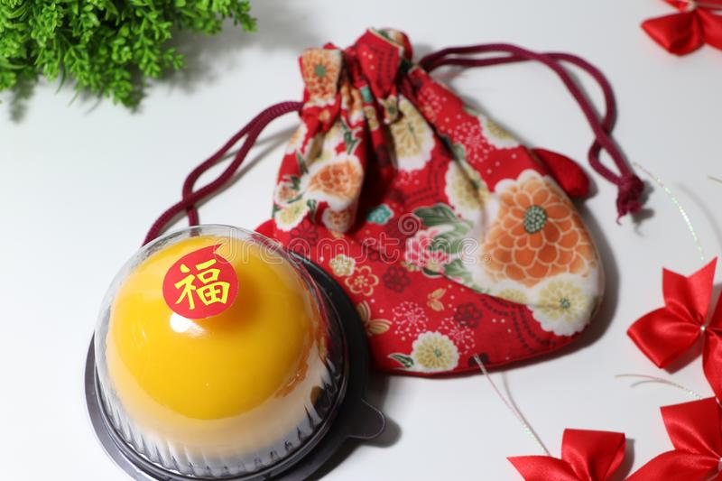 Chinese language : bliss, stick on the orange cake on the red fabric bag and red ribbon and green leaf on white floor. Chinese New Year concept royalty free stock images
