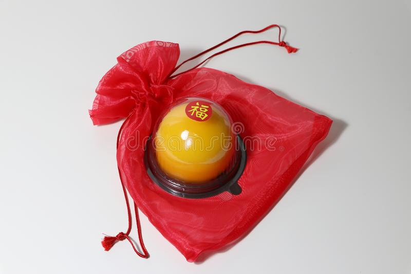 Chinese language : bliss, stick on the orange cake on the red fabric bag on white floor. Chinese New Year concept stock image