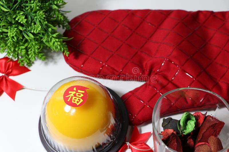 Chinese language : bliss, stick on the orange cake in the red kitchen glove and red ribbon and dried flower and green leaf on. White floor. Chinese New Year royalty free stock images