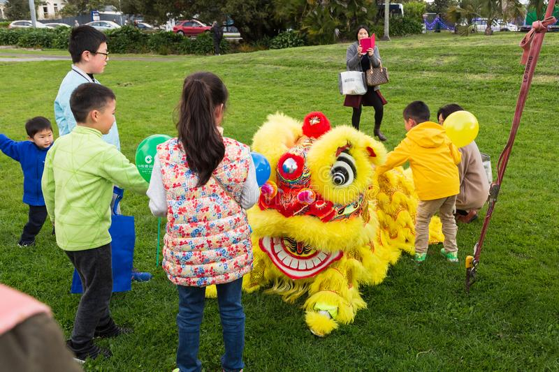 Chinese lion dancers in yellow costume in a park royalty free stock images