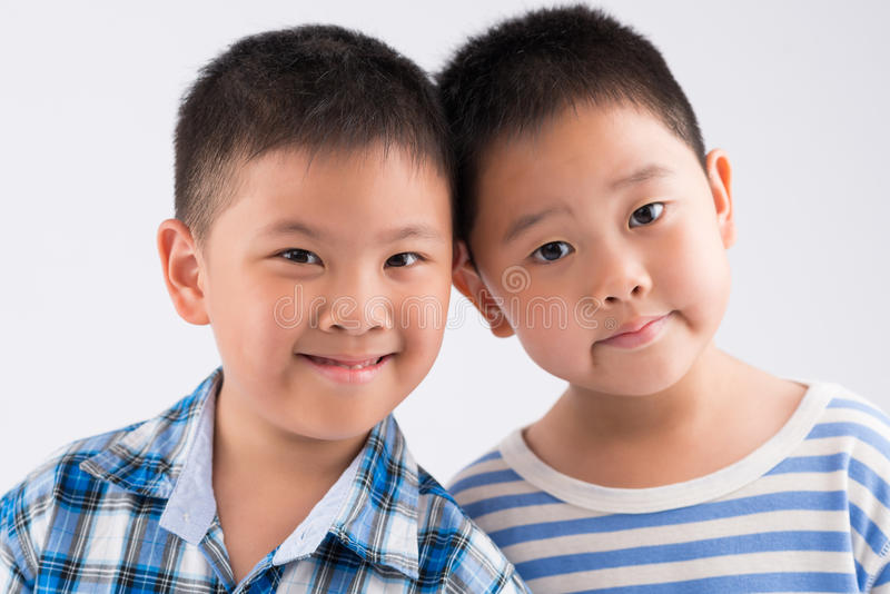 Chinese little brothers. Close-up portrait of two Chinese little brothers looking at the camera stock photo