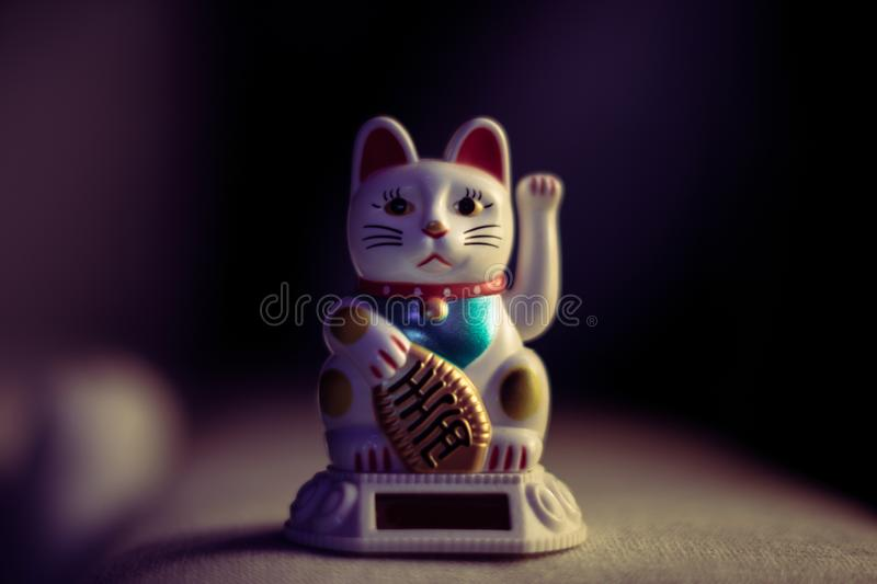 Chinese lucky cat in vintage light stock photos