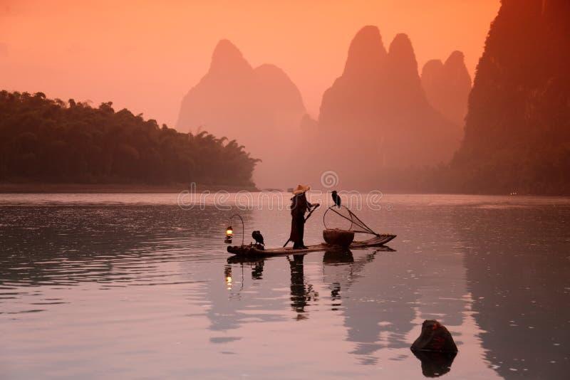 Chinese man fishing with cormorants birds. Yangshuo, Guangxi region, traditional fishing use trained cormorants to fish