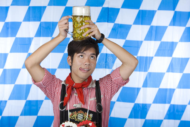 Chinese man Lederhose holds beer stein head. Chinese man dressed with Bavarian Lederhose holds an full Oktoberfest beer stein on his head and looks up. In stock images