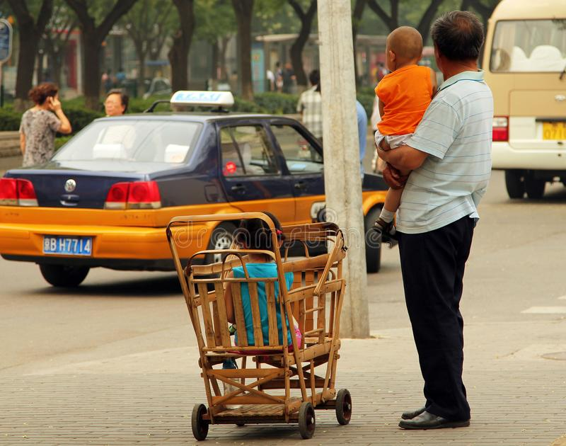 Chinese man with a little child in his arms and another child sitting in a makeshift bamboo stroller royalty free stock photography