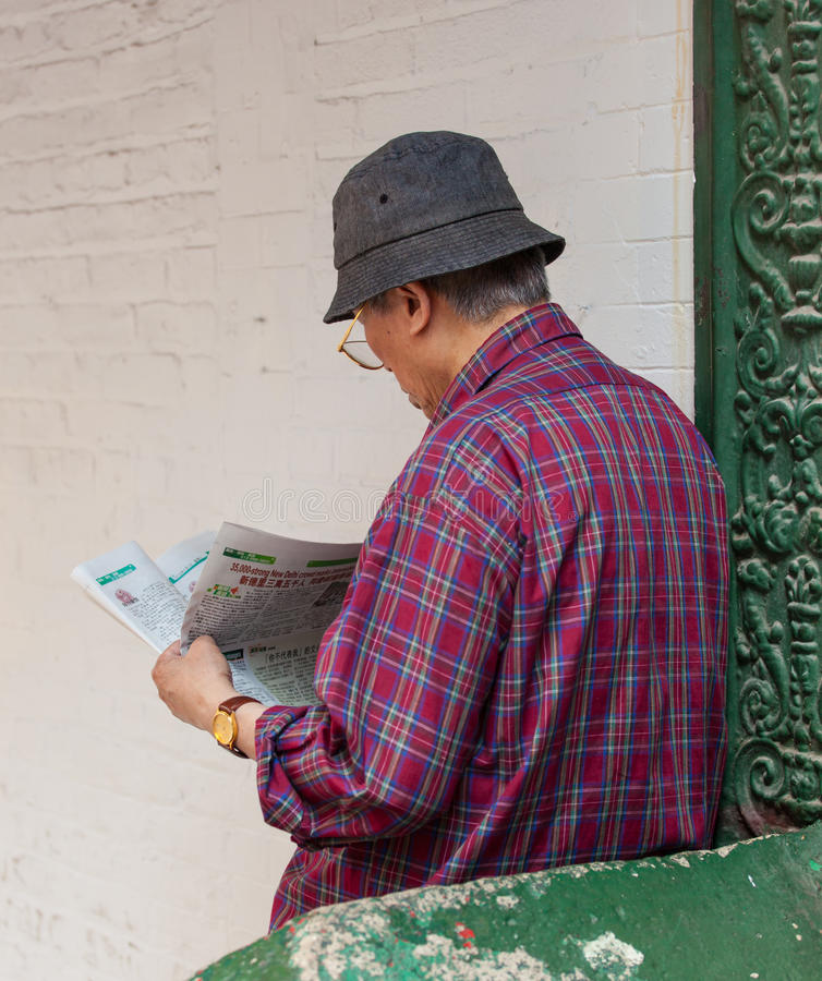 A Chinese man reading the newspaper at Chinatown. stock photo