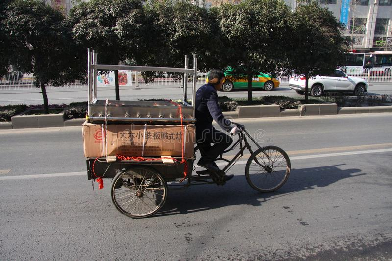 Chinese man riding a cargo tricycle loaded with goods on a roadculture, driving, driver, in China. Cargo bikes or freight tricycl royalty free stock photos