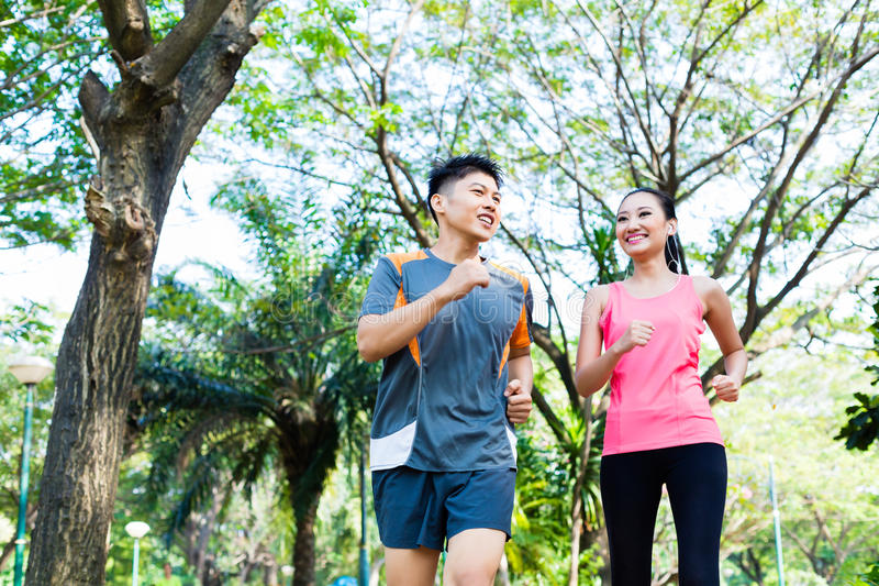 Chinese man and woman jogging in city park royalty free stock images