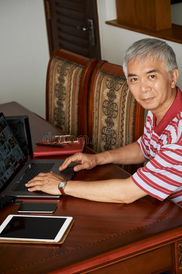 Chinese man working on laptop at home royalty free stock images