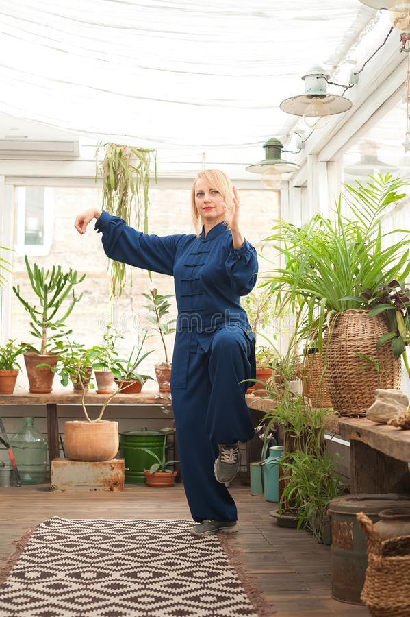 Chinese martial arts tai chi. Woman practicing Taijiquan discipline in a greenhouse with flowers.  royalty free stock image