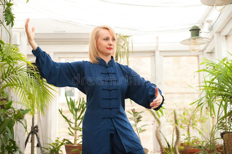 Chinese martial arts tai chi. Woman practicing Taijiquan discipline in a greenhouse with flowers.  royalty free stock images