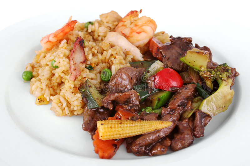 Chinese meal. A meal of beef and black bean sauce served with the chefs special fried rice on a white plate royalty free stock image