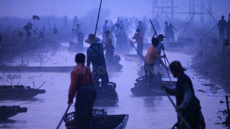Chinese men rows old boat by using the long stick. Yunnan. China. royalty free stock images