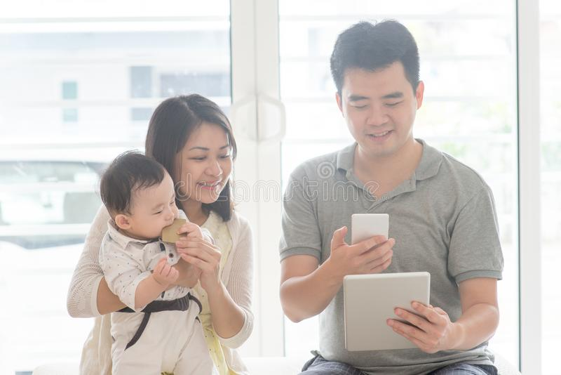 Chinese family scanning QR code. Chinese men scanning QR code with smart phone. Asian family at home, natural living lifestyle indoors royalty free stock photo
