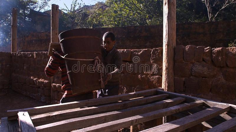 Chinese men working on salt field. Use brine for the salt cooking process. Yunnan. China. royalty free stock photo