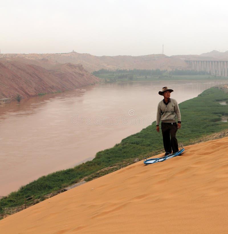 Chinese mens die onderaan de zandheuvel bij de bank van Gele Rivier Huang He gaan glijden stock fotografie