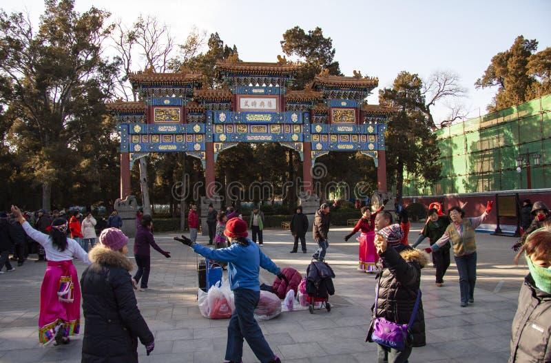Chinese mensen die door een Paifang-Overwelfde galerij in een openbaar vierkant in een park in Peking, China dansen stock foto