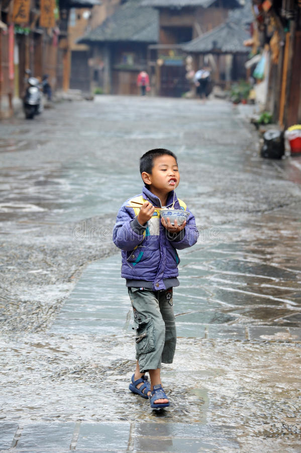 The chinese miao child. Eating Rice noodles ,in Miao Village ( or Villages of Thousands of Miao House-holds) in Xijiang,Kaili,Guizhou,China stock images
