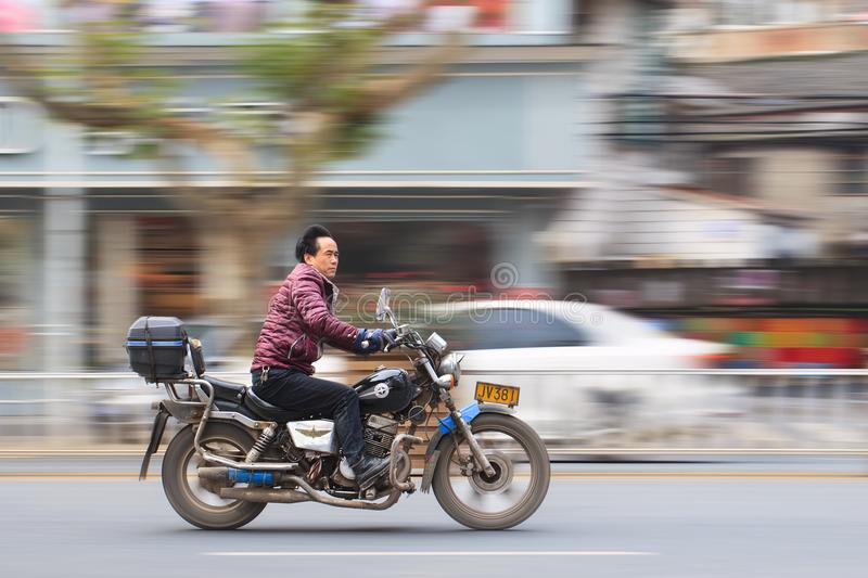 Chinese middel aged man ona motorcycle, Yiwu, China. YIWU-CHINA-JAN. 15, 2016. Chinese man on motorcycle. Large cities, like Beijing and Guangzhou, banned royalty free stock photos