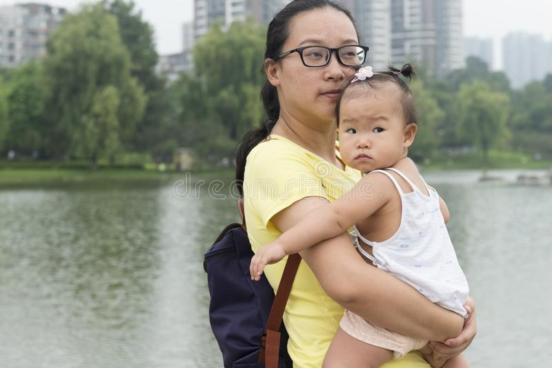 Chinese mom holding daughter in arms in city royalty free stock image