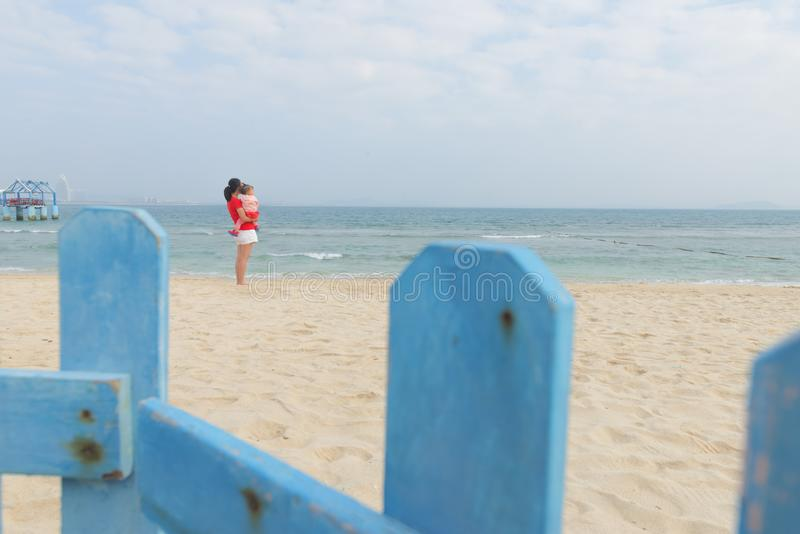 Chinese mom and little daughter watching sea together royalty free stock images