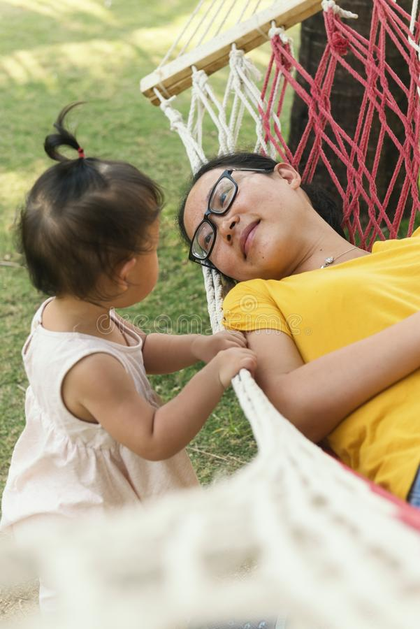 Chinese mom lying on hammock watching daughter stock photography