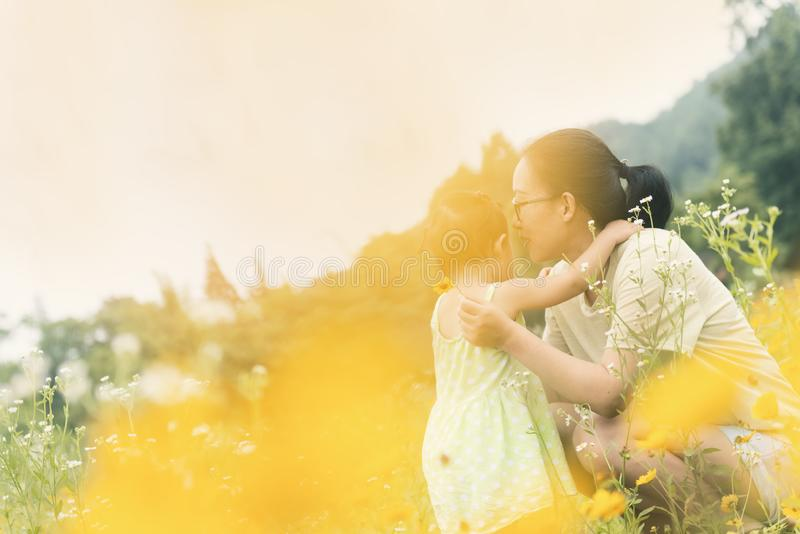 Chinese mom squat comfort little daughter in field stock images