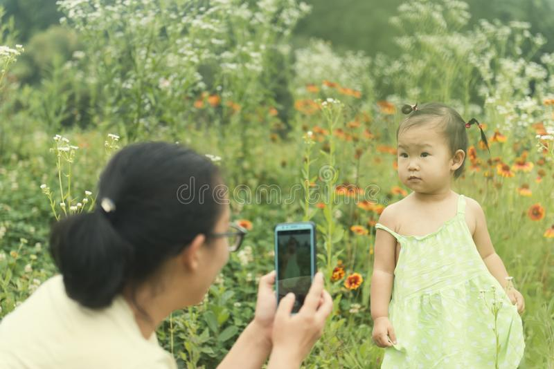 Chinese mom taking photos for little daughter royalty free stock image
