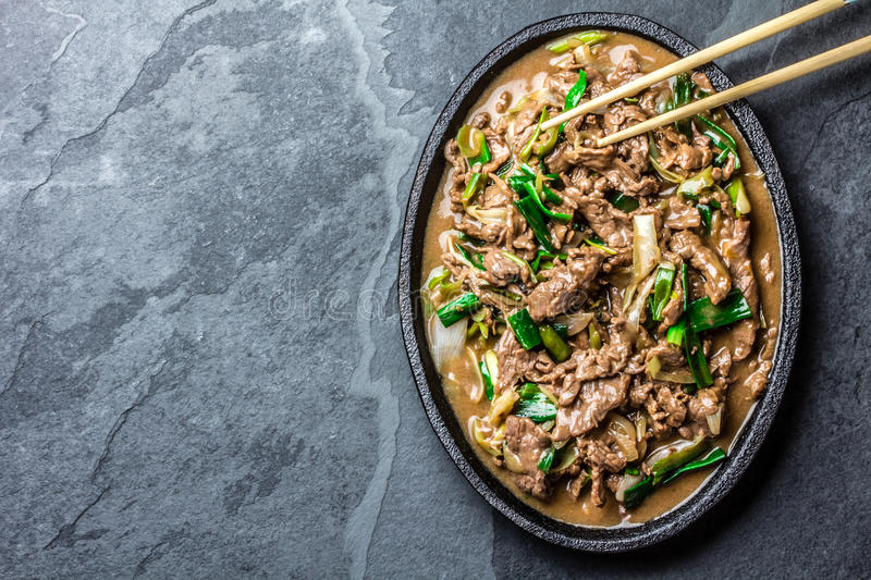 Chinese mongolian beef stir fry on iron plate. Traditional chinese mongolian beef stir fry on iron plate with rice and soya sauce on slate background. Top view royalty free stock image