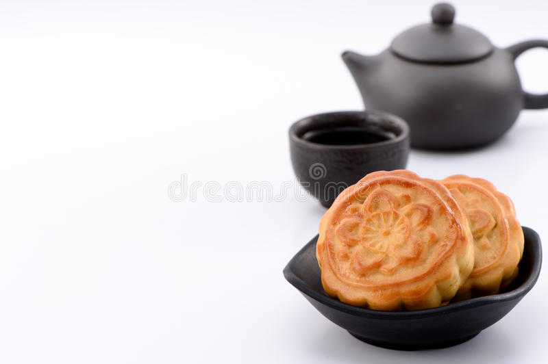 Chinese moon cake -- food for Chinese mid-autumn festival on a black bowl with tea cup and teapot isolated on white background stock image