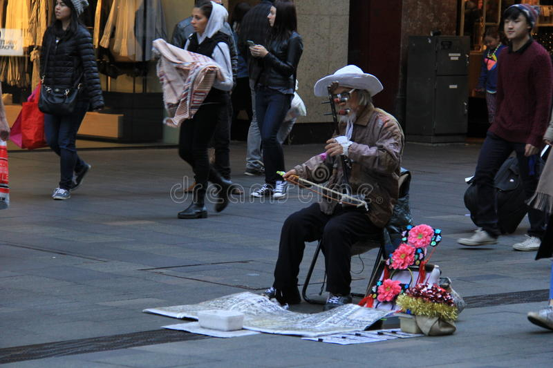 Chinese Musician in Sydney. Old musician plays traditional chinese musical instrument called Erhu or Nanhu, a two-stringed bowed instrument like chinese Violin royalty free stock images