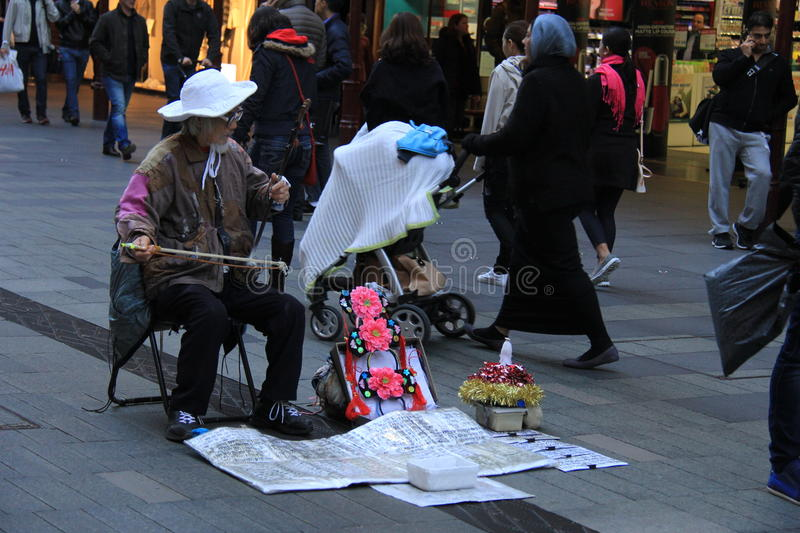 Chinese Musician in Sydney. Old musician plays traditional chinese musical instrument called Erhu or Nanhu, a two-stringed bowed instrument like chinese Violin stock image