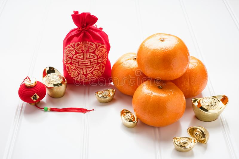 Chinese New year,ang pow red felt fabric bag with gold ingots an. D tangerine oranges on white wood table top,Chinese Language mean Happiness and on ingot mean royalty free stock photography