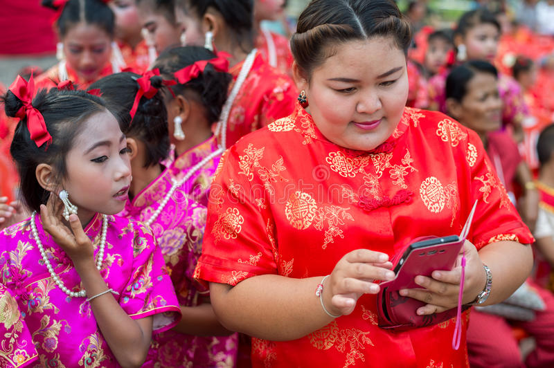 Chinese New Year celebration in Thailand. Hua Hin, Thailand – February 18, 2015: Thai school girl takes a peek at teachers phone during Chinese New Year royalty free stock images