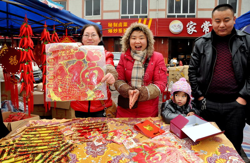 Chinese New Year Celebrations. Family selling colourful paper decorations for the annual Chinese New Year Spring Festival from a table in Long Xing Square in stock photo