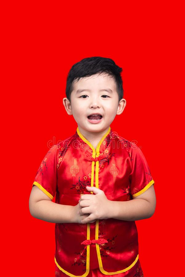 Chinese New Year Concept, Cute Asian boy in red traditional Chinese suit isolated on red with clipping path stock image