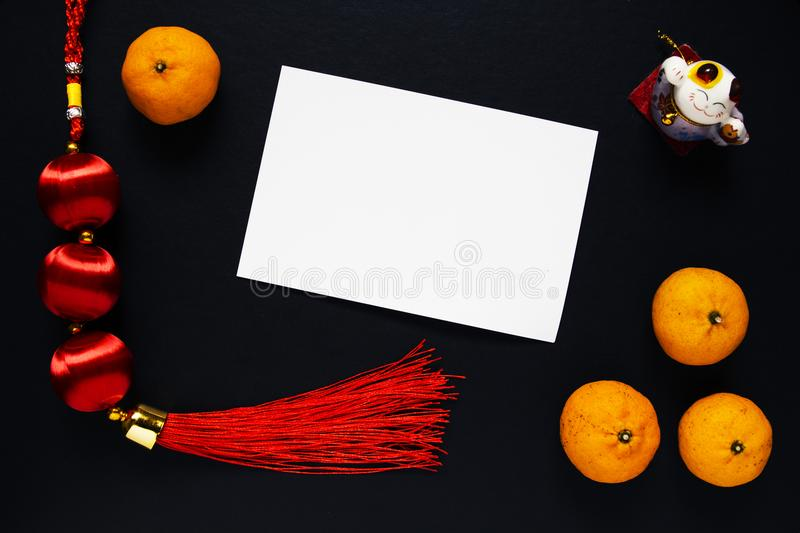 Chinese New Year decor and tangerines on black background with blank postcard. Lunar New Year top view photo. Chinese red lucky knot. Asian winter holiday royalty free stock photography