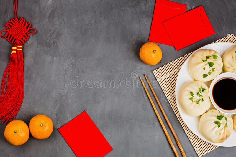 Chinese New Year decoration with dumplings, tangerines, soy sauce, chopsticks, red envelopes on gray concrete background. Happy royalty free stock photos