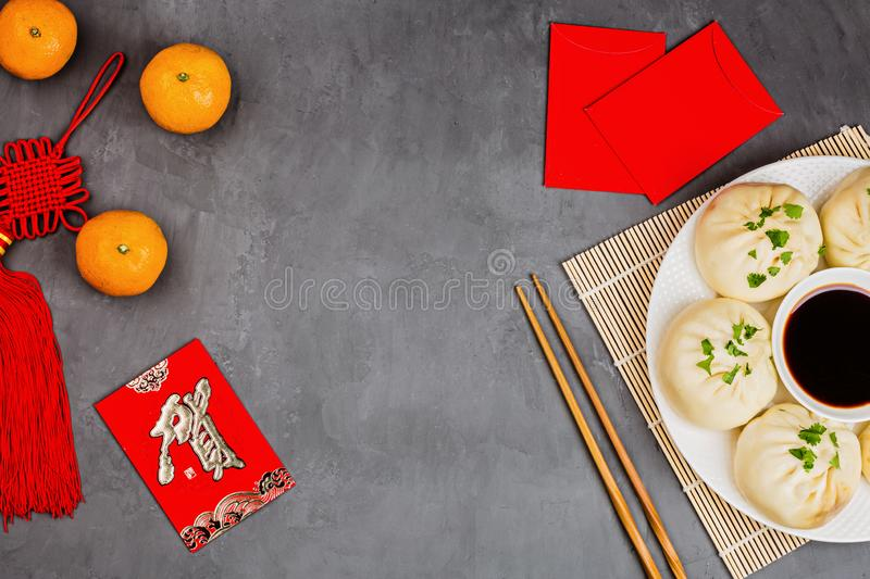 Chinese New Year decoration with dumplings, tangerines, soy sauce, chopsticks, red envelopes on gray concrete background. Happy stock image
