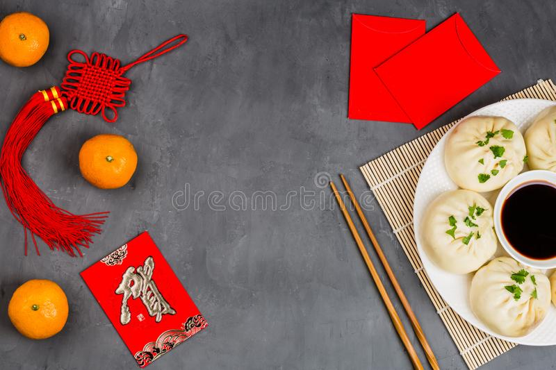 Chinese New Year decoration with dumplings, tangerines, soy sauce, chopsticks, red envelopes on gray concrete background. Happy royalty free stock images