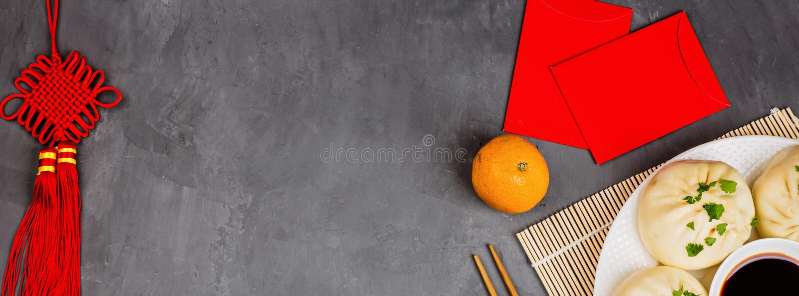 Chinese New Year decoration with dumplings, tangerines, soy sauce, chopsticks, red envelopes on gray concrete background. Happy stock photography