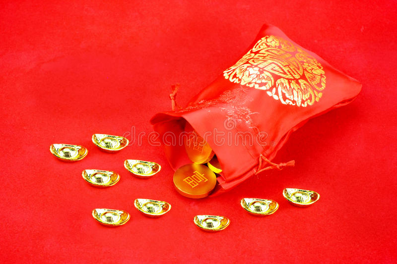 Chinese new year decoration: red fabric packet or ang pow with c. Hinese style pattern and golden coin and ingots on red felt fabric, Chinese text on coin mean ` stock images